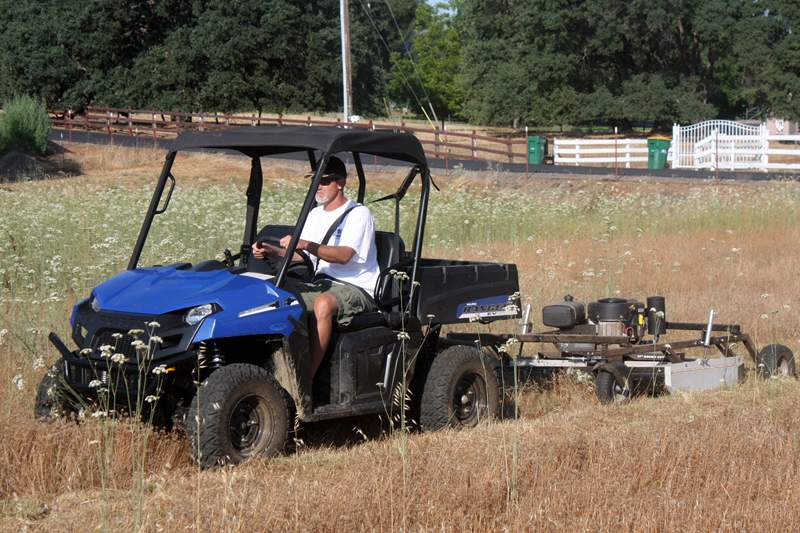 Polaris RANGER EV towing a Kunz Rough Cut Field Mower